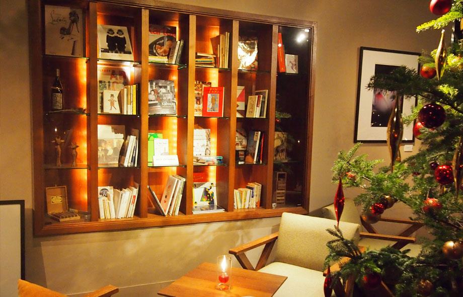 ランプの灯る待合室の本棚には、照明があたりショーウィンドウのような本棚になっています。