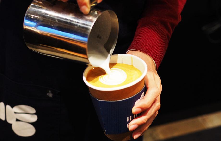 店員がハニーコーヒーのカップを片手にミルクを流しこんでいるのはラテでしょうか?